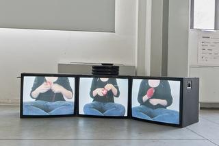 """Workshop e progetto espositivo Academy Awards """"Fuori dalla gabbia di Faraday"""", Marta Pessoni, Cloto, Lachesi e Atropo, video istallazione, 3', 2012  Il filo rosso è narratore di storie, di azioni che si tramandano nel tempo e diventano parte indissolubile del proprio vissuto. Da bambina mia nonna e mia madre mi hanno trasmesso la passione per il ricamo e per il lavoro a maglia; azioni reiterate che sospendono il tempo e fanno riflettere perché isolano il pensiero in un gesto di profonda concentrazione. Avvolgendo il filo di lana rosso attorno ad una sciarpa (il lavoro di mia nonna), a una bavaglino (il lavoro di mia mamma) e alla mia mano, mi riapproprio dei ricordi d'infanzia attraverso il fare che li ha caratterizzati.  Foto di Davide Tremolada"""