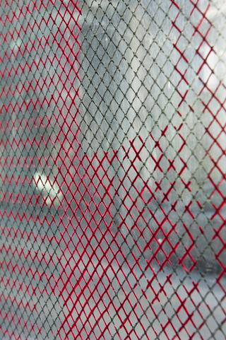 """Workshop e progetto espositivo Academy Awards """"Fuori dalla gabbia di Faraday"""", Matteo Maino, Wire Netting vol. 2, 2012, installazione site specific, marker su pvc, proiettore, cm. 307 x 307 e cm. 408 x 307, 2012  """"La mano non appare mai meno libera di quando deve ricalcare le linee ortogonali della quadrettatura di un foglio."""" (Alighiero Boetti). Wire Netting nasce da una riflessione sul concetto di limite. Ho ipotizzato che, attraverso la creazione di un limite, si apra una porta su elementi e circostanze dapprima non prese in considerazione. Di conseguenza, all'interno di questo vincolo si crea una nuova libertà. Vorrei provare ad innescare questo processo, innanzi tutto, in me stesso, ricalcando la griglia interna ai vetri, in questo caso fittizia. Lo spettatore sarà poi costretto a dare attenzione a ciòche sta all'esterno della galleria,ma attraverso l'evidenziazione del limite fisico stesso dellobspazio, la vetrata.  Foto di Davide Tremolada"""