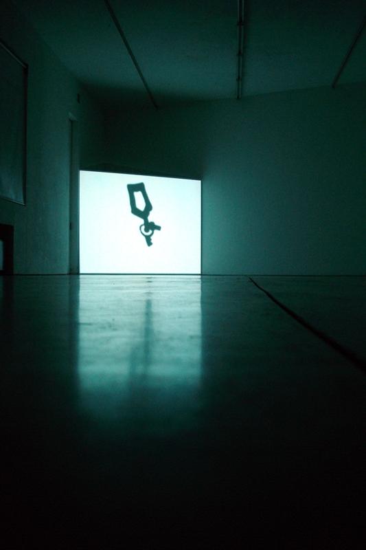 """Video Invitational #3 - Video in tutti i sensi, Giona Bernardi, Key, 2006  Key è il nuovo lavoro video di Giona Bernardi, realizzato con la collaborazione di Ivan Berdondini. Un loop di pochi minuti in cui una chiave ruota initerrottamente. E' quella che viene scaraventata dal personaggio disegnato da Andrea Pazienza in una delle ultime scene di """"Pompeo"""". Nel video la stessa chiave è messa sotto la lente di ingrandimento e compie un movimento rotatorio silenzioso, che nega ogni forma di narratività. Un contocircuito temporale e spaziale che sospende l'azione e crea altri codici della rappresentazione. Una quarta dimensione che suggerisce gli spazi infiniti delle galassie e più precisamente, come afferma l'artista, di Andromeda, l'oggetto celeste più lontano visibile ad occhio nudo."""