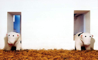 Piero Golia, Le mucche per Morra, 2000: due mucche antistress giganti incastrate nelle porte della galleria; Courtesy Studio Morra, Napoli, foto B. Iodice