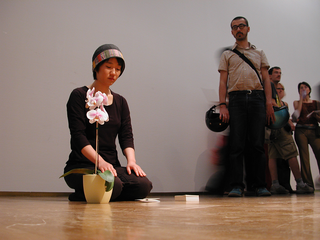 """As soon as possible. Performance loop. The Class of Marina Abramovic - Braunschweig School of Art, Heejung Um, """"Love Odyssey"""".  Artist kneels(on his knees).SHE Takes a white paper and puts it down at the middle of thedistance to the orchid flowerpot. She takes a small piece of bark from the flowerpot and places it on the white paper.he takes another white paper and places it on top of the piece of bark (sandwich). This action is repeated. She builds the tower with papers and pieces of bark from the orchid flowerpot."""