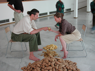 """As soon as possible. Performance loop. The Class of Marina Abramovic - Braunschweig School of Art, Lotte Lindner and Till Steinbrenne, """"Family II"""".  Lotte Lindner and Till Steinbrenner´s work is characterised by their craftsmanship background. Both are sculptors as well as performers. In their performances work and its products play a prominent role. This not only means material but as well immaterial products as sound for example. These """"products"""" are produced by hands and bodies. In """"Family II"""" the artists peal a huge pile of potatoes together: one holds the knife, the other the potato. This means the top of collaboration. It asumes great trust and a great sensibility for the other. The potato stands for food in general and it gives the picture back the simplicity of a Breughel genre painting.  Lotte Lindner and Till Steinbrenner´s collaboration work started in early2002 when both met in the class of Marina Abramovic. Lindner and Steinbrenner live and work in Hannover, Germany."""