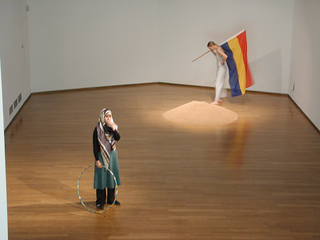 """As soon as possible. Performance loop. The Class of Marina Abramovic - Braunschweig School of Art, Nezaket Ekici, Irina Thorman, """"Join us now"""".  For two years now Irina Thorman and Roland P. Runge have been working on the issue of nationalism and patriotism. They use strong slogan-like symbols in order to trace back the character of national and patriotic gestures.  Red-yellow-blue, the primary colors in painting make up the flag in their work. This flag could represent any country.  Nezaket Ekici born 1970 in turkey and lives sinces 1973 in Germany. She is a artist from two cultures and lives and works in Berlin.  She finished her Master in Arthistory and Artpedagogy. Since 2000 she study by Marina Abramovic at the HBK Braunschweig.  Ekici has been participating in various international and national Groupexibitions and artist Workshops in Germany and Europe. She has worked with international Artist like Ilya Kabakov and Tania Bruguera.  Irina Thorman born 1971 in Ratzeburg. She studied arttherapy at the Fachhochschule Ottersberg from 1994-1998 and finished with diploma. She lives and works as arttherapist and artist in the country of North-Germany. Since 1998 she studying with Marina Abramovic at the Kunsthochschule Braunschweig. Irina Thorman has participated in various exhibitions and projekts, for example: Projektraum, artwork of living, www.projektraum-berlin.de, Berlin, from 1999 to Feb. 2001 Virus, Theaterprojekt, Theater am Halleschen Ufer, Berlin u. Pumpenhaus, Münster, 2000 art migration, Nationalmuseum, Stettin, Polen, 2000 Wer hat Angst vor Rogger Whittacker?, Kunstverein """"Freunde aktueller Kunst"""", Zwickau, 2001""""prêt-á-perform"""", class of Marina Abramovic, Galerie Viafarini, Mailand, 2002"""