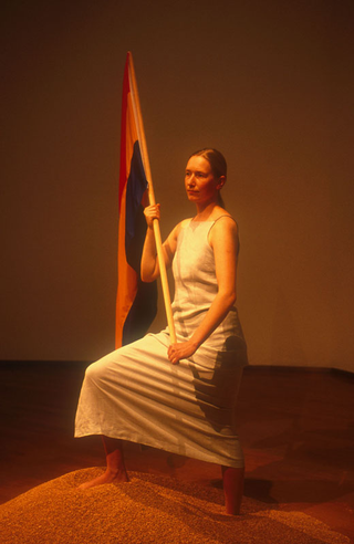 """As soon as possible. Performance loop. The Class of Marina Abramovic - Braunschweig School of Art, Irina Thorman, """"Join Us Now"""".  Irina Thorman born 1971 in Ratzeburg. She studied arttherapy at the Fachhochschule Ottersberg from 1994-1998 and finished with diploma. She lives and works as arttherapist and artist in the country of North-Germany. Since 1998 she studying with Marina Abramovic at the Kunsthochschule Braunschweig. Irina Thorman has participated in various exhibitions and projekts, for example:  Projektraum, artwork of living, www.projektraum-berlin.de, Berlin, from 1999 to Feb. 2001  Virus, Theaterprojekt, Theater am Halleschen Ufer, Berlin u. Pumpenhaus, Münster, 2000  art migration, Nationalmuseum, Stettin, Polen, 2000, Wer hat Angst vor Rogger Whittacker?, Kunstverein """"Freunde aktueller Kunst"""", Zwickau, 2001 """"prêt-á-perform"""", class of Marina Abramovic, Galerie Viafarini, Mailand, 2002  For two years now Irina Thorman and Roland P. Runge have been working on the issue of nationalism and patriotism. They use strong slogan-like symbols in order to trace back the character of national and patriotic gestures.  Red-yellow-blue, the primary colors in painting make up the flag in their work. This flag could represent any country.  The projekt Join Us Now in Milano contain 3 works. Two video loops are projected life-sized in a room at one wall. At the same time the live performance fatherlandssongs will be shown outside from the museum.  In the performance fatherlandssongs Irina Thorman and Roland P. Runge are working with archaic symbols. With the two videoprojektions family and fatherland has burnt down they playing with the stereotype family: father, mother, child; and with the confrontation of dreariness with hope. All three works circle around a human desire, which find expression in national and patriotic gestures. The sound of the work is created out of statements from homepagevisitors of www.joinusnow.org."""