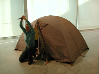 """As soon as possible. Performance loop. The Class of Marina Abramovic - Braunschweig School of Art, Lotte Lindner, """"Mountain"""".  The performative installation shows a room in a room: a tent as the smallest private space. You can not find out what the performer does inside. At the same time it becomes a sculpture itself. Room will be inside and out as the performer comes out of the tent from time to time only to show his pride: this is the conquest of time and space.  The performer Lotte Lindner is born 1971 in Bremen, Germany. She lives and works in Hannover. At Braunschweig School of Arts she studied sculpture, since 2000 she studied with Marina Abramovic. In 2003 she finished artschool.  She understands performance as a possibility for temporary sculpture."""