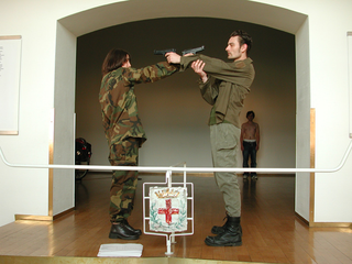 """As soon as possible. Performance loop. The Class of Marina Abramovic - Braunschweig School of Art, Daniel Mueller-Friedrichsen e Susanne Winterling, """"Steady state"""".  Each gun is target and agressor : steady state- no movement possible.The piece of the two Berlin based artists is a reaction on the contempory political situation.  Collaborative work with Susanne Winterling at transart02, Brixen, Italy 2002"""