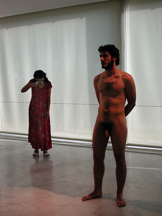 """As soon as possible. Performance loop. The Class of Marina Abramovic - Braunschweig School of Art, Yingmei Duan, """"Friend"""".  """"Sexuality is very important in every society. Sexuality is similar to science and ritual. Each society system instructs different rituals. Sexuality concerns not only the family but also religion, philosophy, psychology and so on.""""  Chinenish artist Yingmei Duan has told us """"There is totally another cultur. We haven't sexsual education in the school of my country. Before I was 21 years old, I really knew nothing about sex and I have never spoken the word about """"Sex"""". I have a lot of questions in my mind at that time, for example: """" Why does woman become pregnant?"""" """"Where do I come from?"""" """" why do my parents make a quarrel?"""" Until my girlfriend asked me, what I knew about sex? I was very busy since that day.""""  Description of the Performance: A naked man stands in a spotlight in the middle of the room. He looks in the direction of public. Birds ton from Forest sounds and I come in from one side of the room. I wear a pink dress and glasses. I am looking for something with the magnifying glass and stealthy go to the man. I am shy to see penis back und forth und very curios about penis of man und check it through the magnifying glass. After I have finished my intensiv studies of penis, I leave the room thoughtfully.  1970 born in Shenyang, Liaoning Province/ China.    Education  1987-1989 Studies of oil exploration at the Northeast Petroleum University, China; 1991-1993 Advanced studies in oil painting and mural painting at the Central Academy of Fine Arts in Beijing; 1996-1997 Advanced studies in sculpture at the Central Academy of Applied Arts in Beijing; Since 1999 Studies at the Academy of Fine Arts in Braunschweig, Germany at Prof. Nobert Tadeusz und Mara Mattuschka; Seit 2000 at Prof. Birgit Hein and Marina Abramovic."""