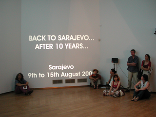 """As soon as possible. Performance loop. The Class of Marina Abramovic - Braunschweig School of Art, Ivan Civic, """"Back in Sarajevo... after 10 years..."""".  Back in sarajevo... after 10 years... is a live performance where the artist Ivan Civic presents his return to his native town... Sarajevo. A video projection is beamed on a wall, above the ground. Coming out of the wall there is a metal construction on which the performer can """"virtualy"""" step into the filmed city and interact with what he has filmed live from the 9th till the 15th of August 2002. The video is five hours long and during that time the rests of the city, relatives and friends will be portrayed through a non stop, live, new expierience. The performance lasts as long as the video does, without a pause.  IVAN CIVIC, born 30.06.1979    Studies:  Liceo scientifico """"Giorgio dal Piaz"""", Feltre, Italy 1994-1999 Hochschule für Bildende Künste, Braunschweig, Germany since 1999.  Born in Sarajevo, Bosnia and Herzegovina, 30.06.1979.  Primary studies in New York, U.S.A. and Sarajevo. Secondary school in Italy. Currently studies art at the Highschool of fine arts in Braunschweig, Germany by Marina Abramovic (Performance) and Birgit Hein (experimental video and film)."""