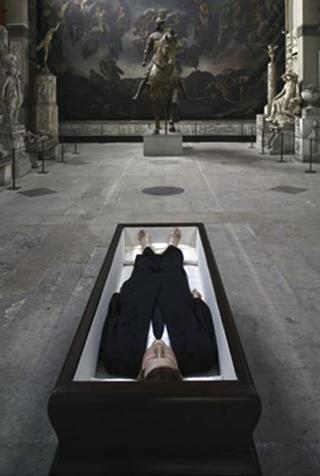 Maurizio Cattelan, Now, 2004 Polyester resin, wax, human hair, fabric, coffin 85 x 225 x 78 cm ARC / Musee d'Art Moderne de la Ville de Paris at the Chapelle des Petits Augustins, Ecole nationale superieure des beaux-arts Courtesy:Marian Goodman Gallery, New York