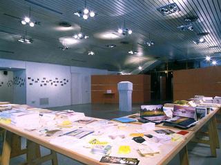 Vito Acconci. Arte, architettura e design verso lo spazio pubblico - Un confronto con la situazione della Public Art in Italia nel lavoro di 60 artisti italiani. Conferenza di Vito Acconci 14 aprile, LUCA VITONE - WIDE CITY , MILANO, 1998.  C'è una torre a Milano chiamata Velasca intorno alla quale ruota la città. E' alta più di venti piani e s'innalza sulle case attorno come un fungo protettivo. B.B.P.R. l'hanno disegnata dopo la guerra e rimane l'architettura milanese che meglio rappresenta questo secolo. È così che il progetto ruota intorno ad essa o meglio ad un suo modello che, posto al centro della mostra, distribuiva ciò che vi abita all'interno. E' una cartina di Milano come quelle che si trovano negli uffici turistici della città, come quelle stampate dalla Di Lauro (anche questa lo è), tirata a 23.000 copie e distribuita anch'essa nei suddetti uffici.Ma c'è un elemento che la differenzia dalle altre, non di carattere cartografico, ma informativo: contiene una lista di circa 500 indirizzi di attività straniere operanti a Milano, affiancati dalle coordinate che ne individuano la posizione. Sono le attività che più o meno ufficialmente si sono sviluppate negli ultimi quindici anni attorno alla torre: consolati, centri culturali, ristoranti, noleggio video, istituti, associazioni, negozi di cosmesi, dischi, alimentari e abbigliamento, sedi di comunità, templi religiosi e take-away. Ognuno, individualmente, secondo i propri interessi e desideri, può intraprendere un proprio percorso e visitare, frequentare e utilizzare tali indirizzi.Ma un altro itinerario, più mirato, è stato organizzato a fine mostra per quattro mercoledì di aprile: un'introduzione all'attività dei diversi centri culturali stranieri a Milano. Arrivati lì, a piedi o con un mezzo pubblico messo a disposizione dell'ATM, un rappresentante ci introduceva sulle loro attività, sui perché, sulle relazioni che con il loro operare intrattengono con la loro e le altre comunità. Ognuno poteva iscriversi 